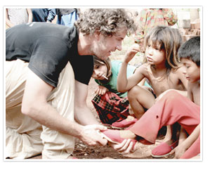Blake Mycoskie putting a shoe on a child's foot in a remote town of Argentina