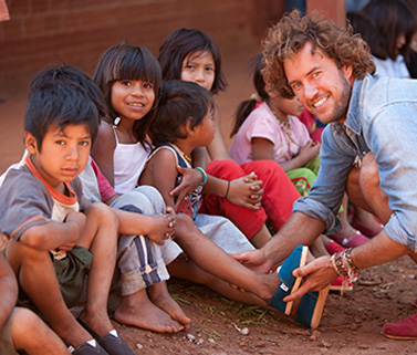 Blake Mycoskie putting a shoe on a young hispanic child's foot sitting on the ground among many other children